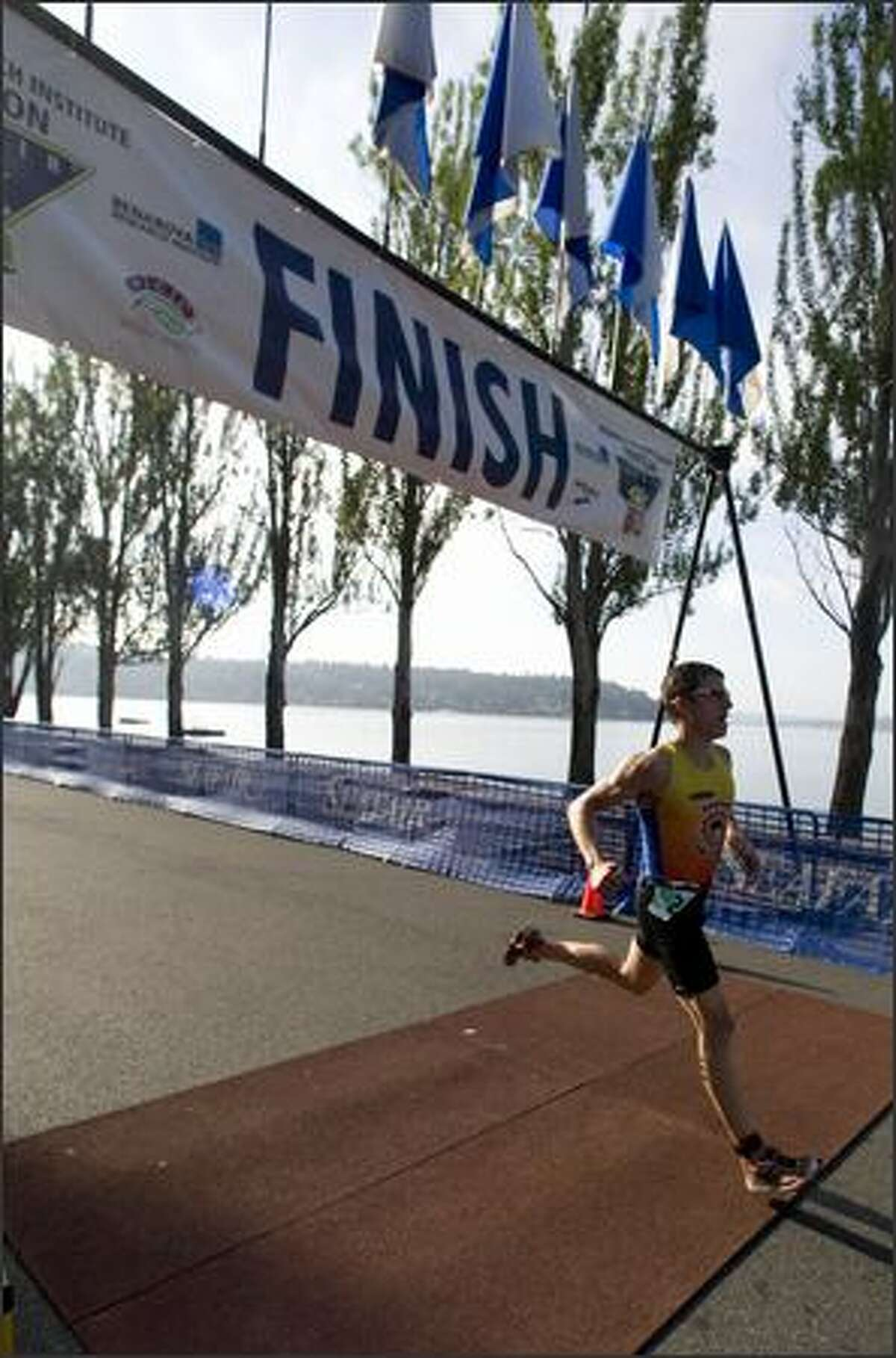 Chris Tremonte, of Redmond, crosses the finish line to place first with a time of 59.09 in the 2008 Benaroya Research Institute Triathlon.