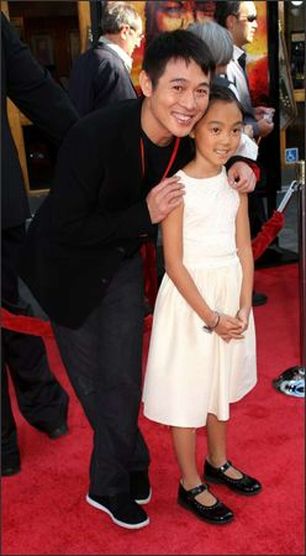 """Actor Jet Li (L) and his guest attend the premiere of Universal Picture's """"The Mummy: Tomb of the Dragon Emperor"""" at the Gibson Amphitheatre at Universal City Walk in Los Angeles, California."""