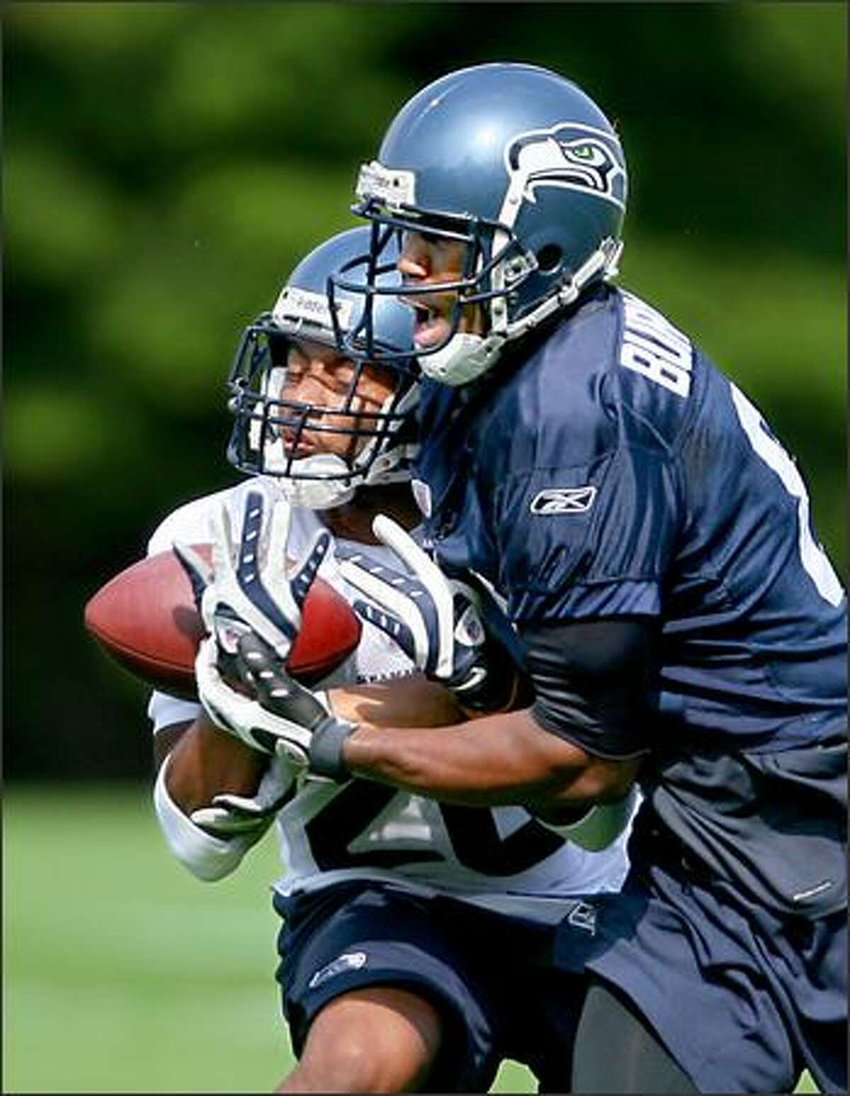 Wide receiver Nate Burleson (right) battles with cornerback Josh Wilson for a pass as Wilson knocked the ball to the ground as the Seattle Seahawks hold the first practice of their 2008 season training camp at their Kirkland, Wash., headquarters Friday.