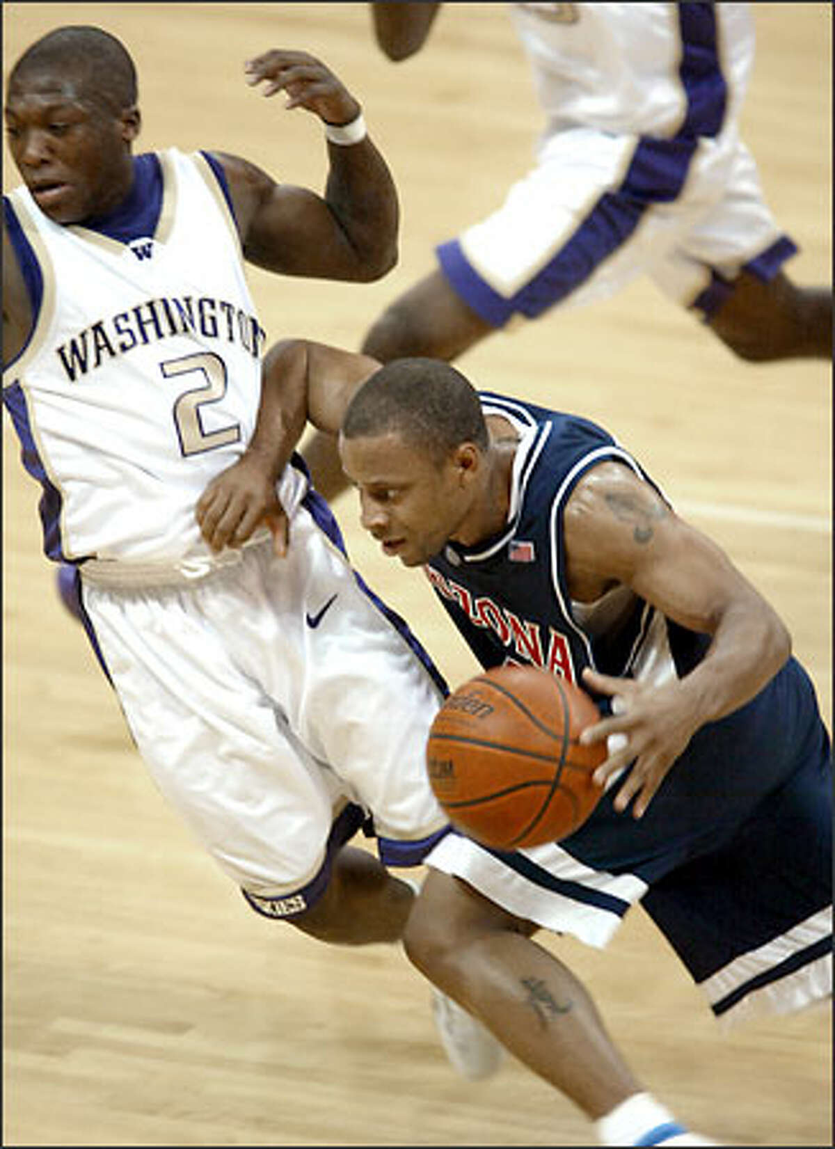 Arizona point guard Jason Gardner maneuvers against Nate Robinson.