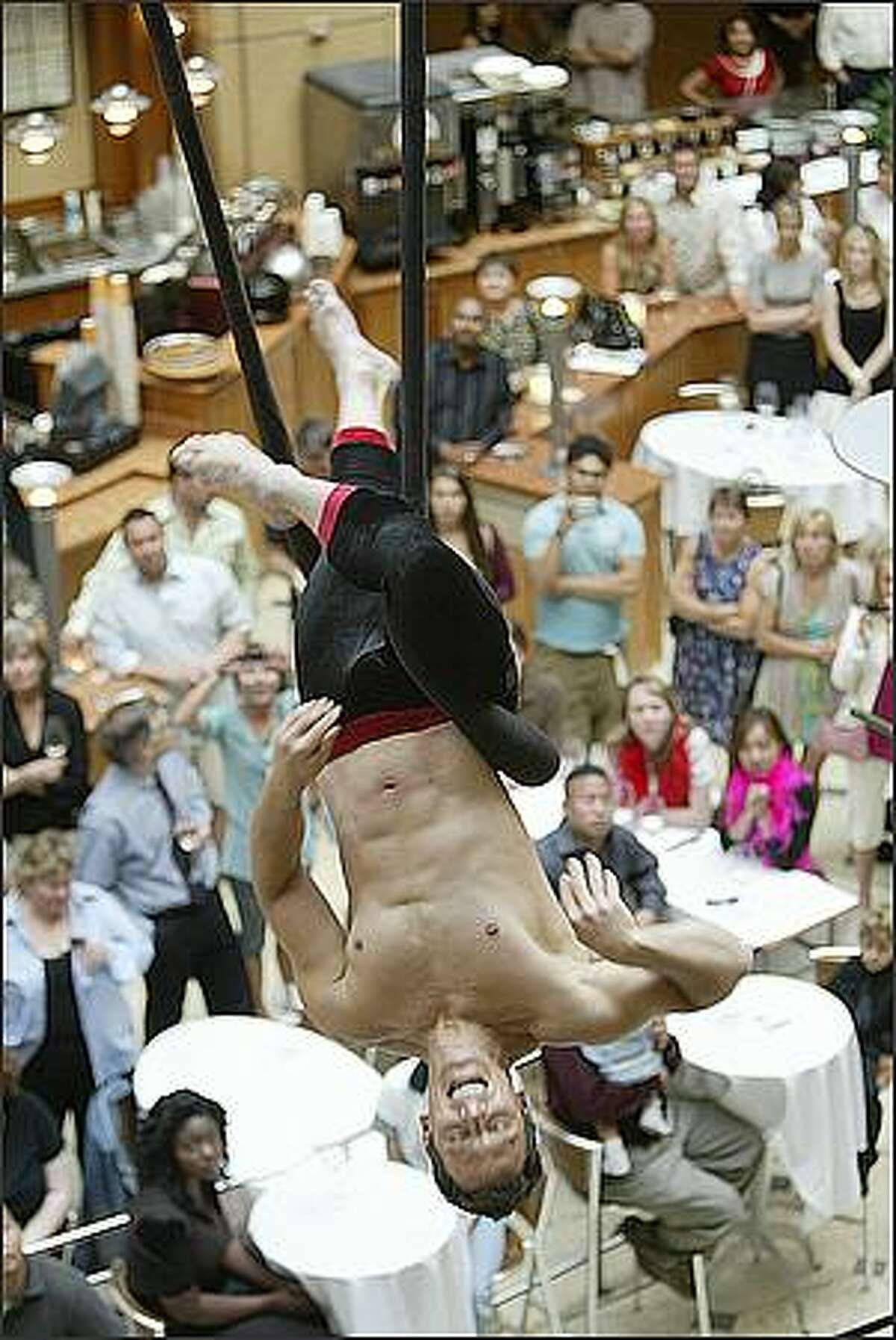 """World class trapeze artist Eric Newton swings around above the crowd during the sneak performance of Teatro ZinZanni and Pacific Place presentation of """"Aerial Antics in the Atrium."""""""
