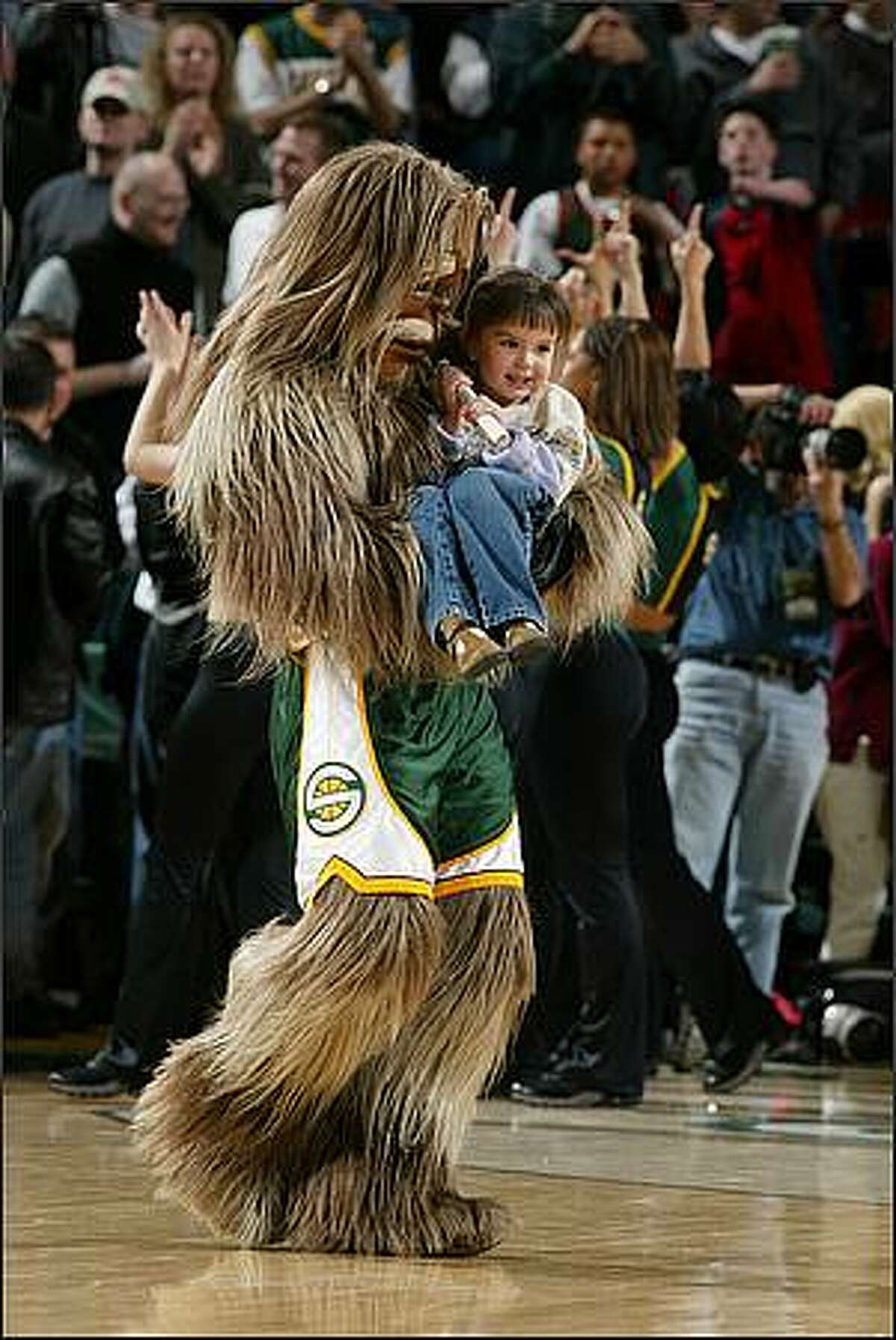 Sonics Mascot Squatch brings a young fan out onto the court during a break in the game between the Memphis Grizzlies and Seattle Sonics. March, 27 2002.