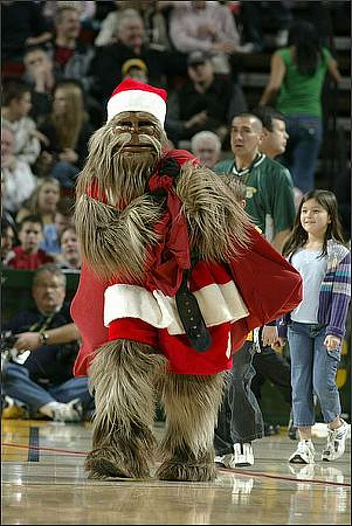 Team mascot Squatch, dressed as Santa Squatch, carries his bag of goodies onto the court during a time out against the Denver Nuggets. Dec 22, 2004