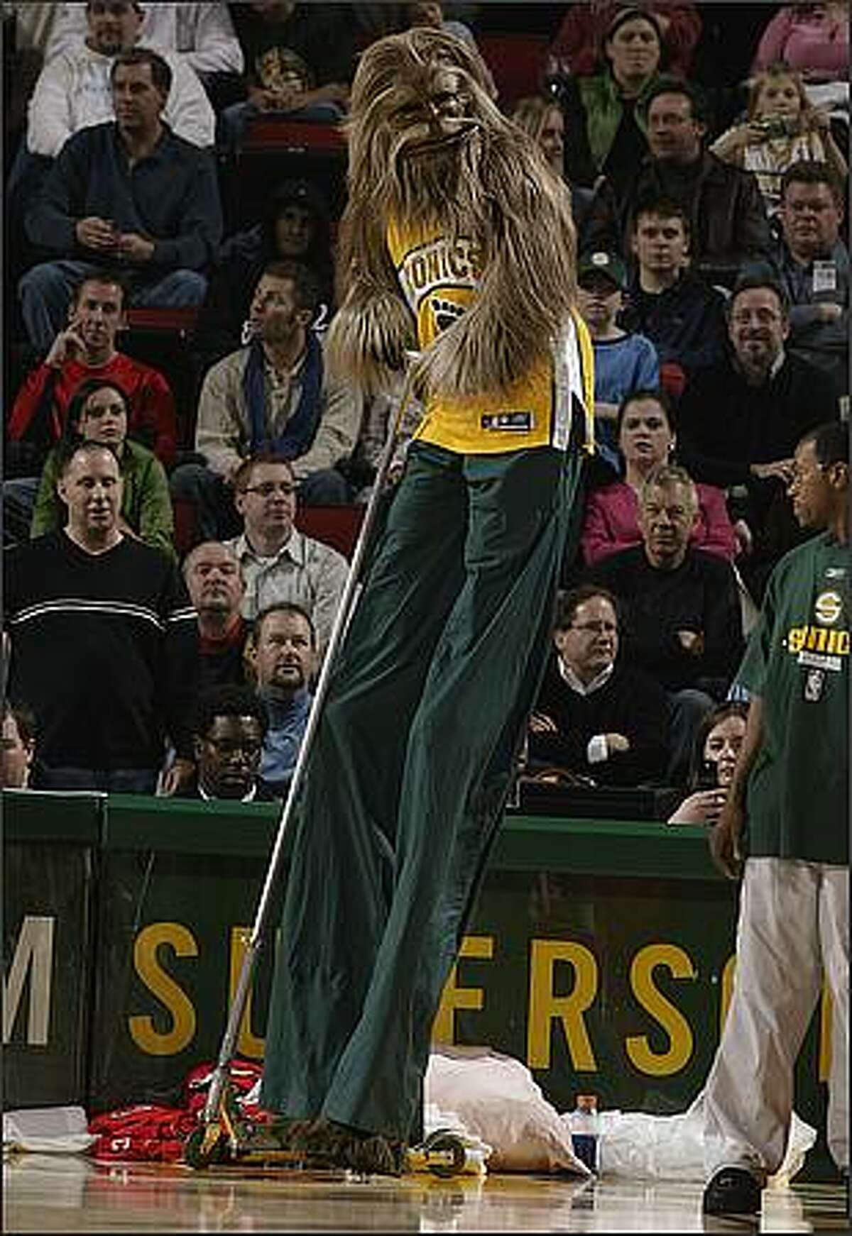 Squatch rides a scooter wearing stilts under his long pants during a break in the action against the Houston Rockets. December 15, 2005.