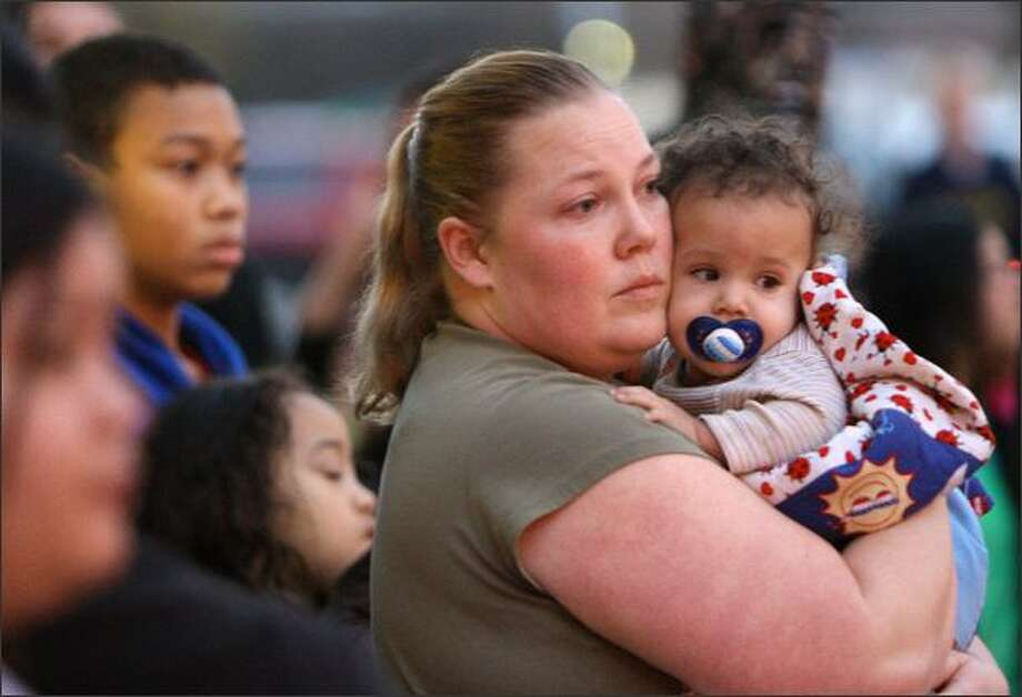 Molly Reyes of Renton holds her son Kendrick, 7 months, while watching police clear Southcenter Mall after a shooting. Reyes said she was shopping when she heard two shots, then ran with a crowd into a store and hid for about 20 minutes until police came and escorted them out of the mall. Photo: Mike Kane/Seattle Post-Intelligencer