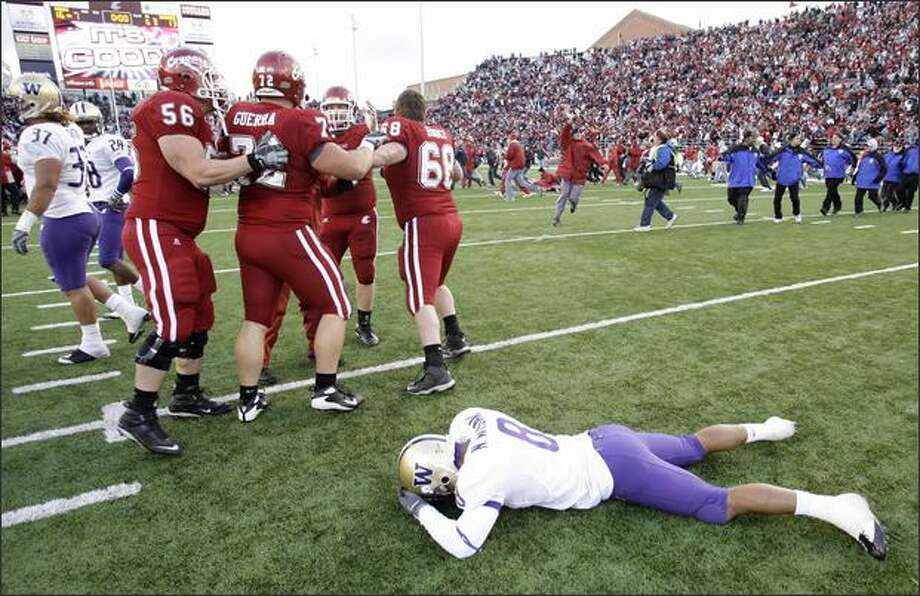 Washington free safety Nate Williams lies on the ground as Washington State players celebrate their 16-13 win over Washington in double overtime. Photo: / Associated Press