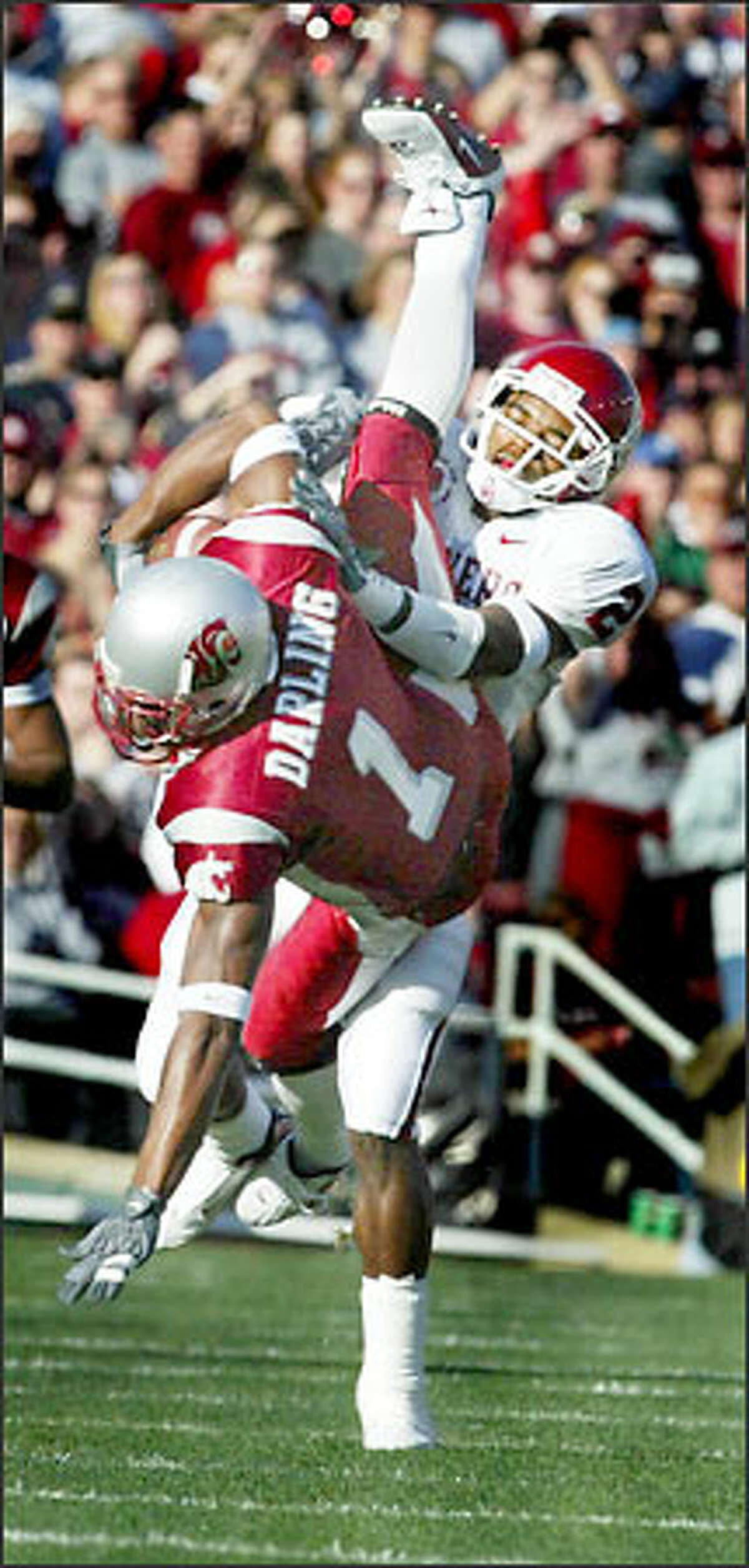WSU's Devard Darling, who caught five passes for 75 yards, is upended by Oklahoma cornerback Derrick Strait.