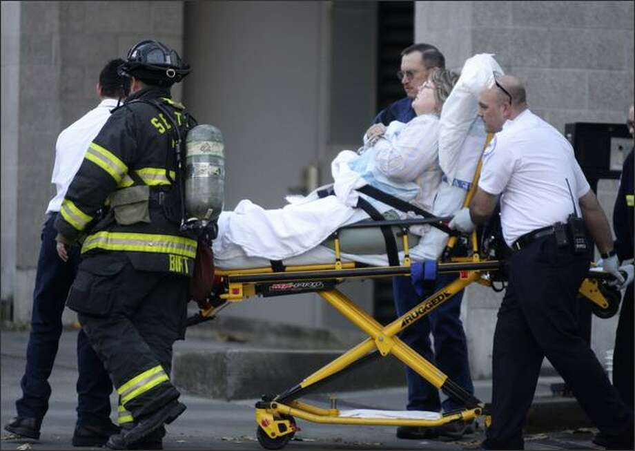 Emergency workers evacuate a woman from the 911 dispatch center in Seattle on Monday after several workers reported becoming ill. Photo: Andy Rogers/Seattle Post-Intelligencer