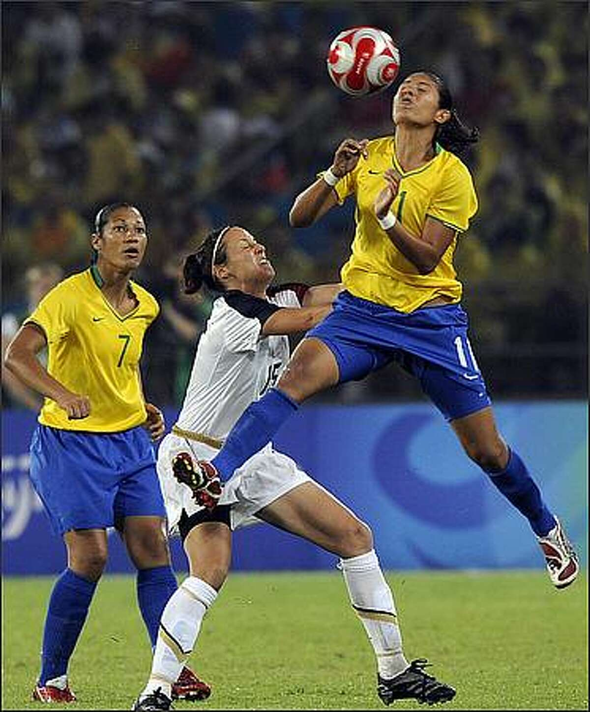 Brazil's Cristiane (R) vies for the ball with Kate Markgraf (C) of US while Brazil's Daniela looks on during the 2008 Beijing Olympic Games women's football Gold medal match at the Workers Stadium in Beijing.
