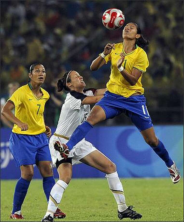 Brazil's Cristiane (R) vies for the ball with Kate Markgraf (C) of US while Brazil's Daniela looks on during the 2008 Beijing Olympic Games women's football Gold medal match at the Workers Stadium in Beijing. Photo: Getty Images