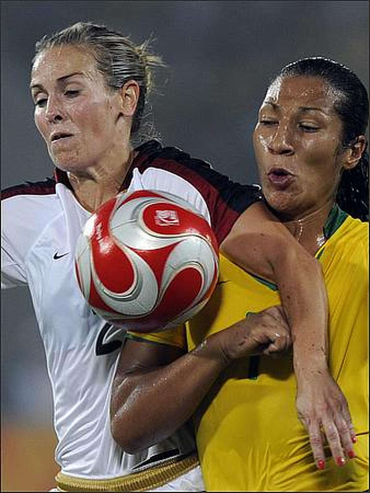 Daniela (R) of Brazil vies for the ball with Heather Mitts of US during the women's gold medal football match in the 2008 Beijing Olympic Games in Beijing.