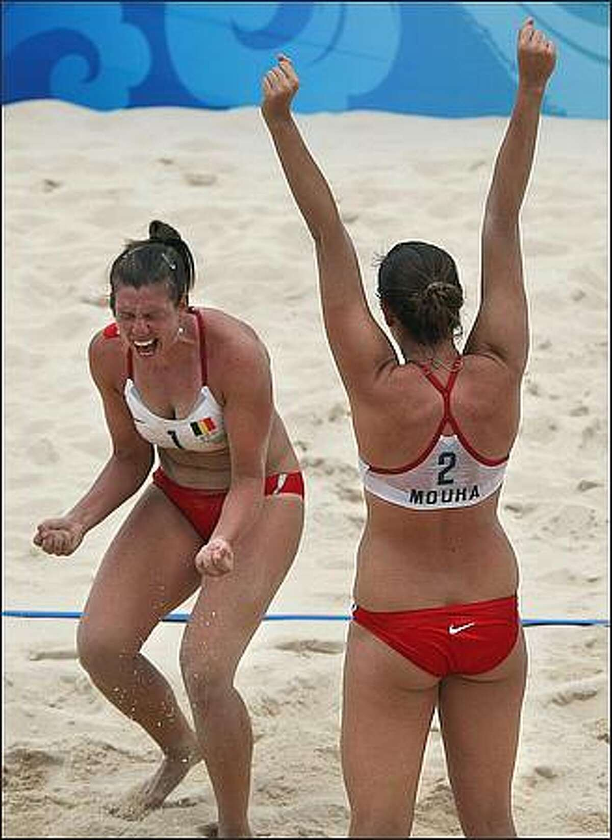 Belgium's Liesbet Van Breedam and Liesbeth Mouha (R) celebrate after beating Switzerland 2-0 in their Women's preliminary beach volleyball match at Beijing's Chaoyang Park Beach Volleyball Ground during the 2008 Beijing Olympic Games. (Photo THOMAS COEX/AFP/Getty Images)
