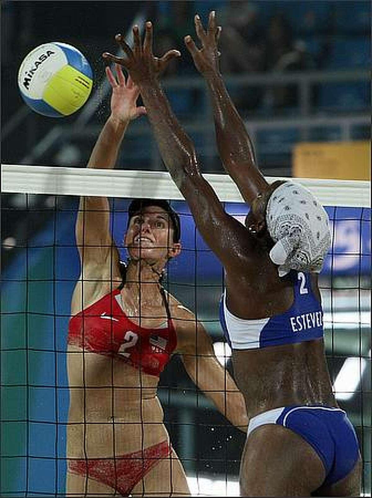 Elaine Youngs (L) of US smashes the ball against Cuba's Imara Esteves Ribalta in their Women's preliminary beach volleyball match at Beijing's Chaoyang Park Beach Volleyball Ground during the 2008 Beijing Olympic Games. US won 2-1. (Photo THOMAS COEX/AFP/Getty Images)