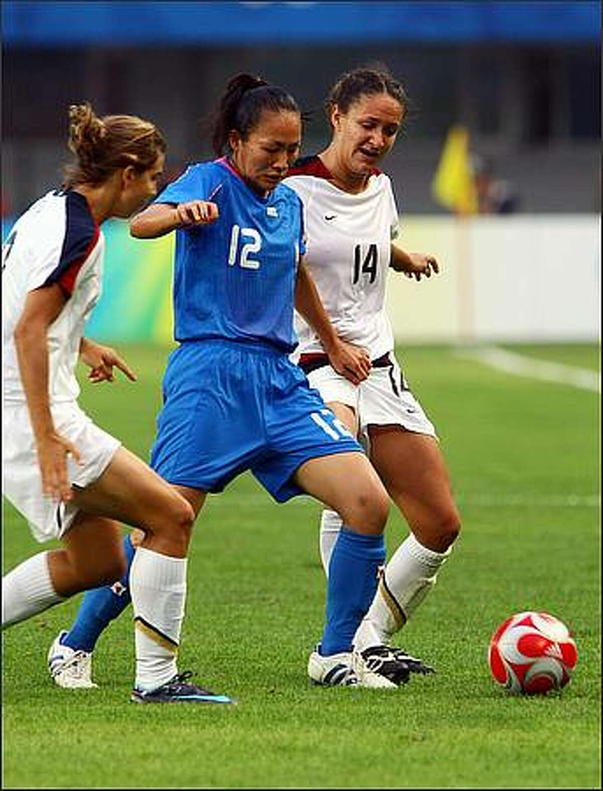 Karina Maruyama (C) of Japan vies with Stephanie Cox (R) of the US during their first round Group G women's football match of the 2008 Beijing Olympic Games at the Qinghuangdao Olympic Stadium. The defending US team defeated Japan by 1-0.