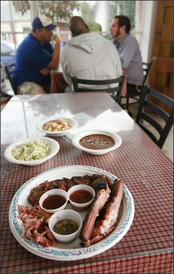The half sampler, with brisket, pork shoulder, ribs, flank steak and three sauces, plus coleslaw, potato salad and baked beans, costs $14.25. Photo: Paul Joseph Brown/Seattle Post-Intelligencer