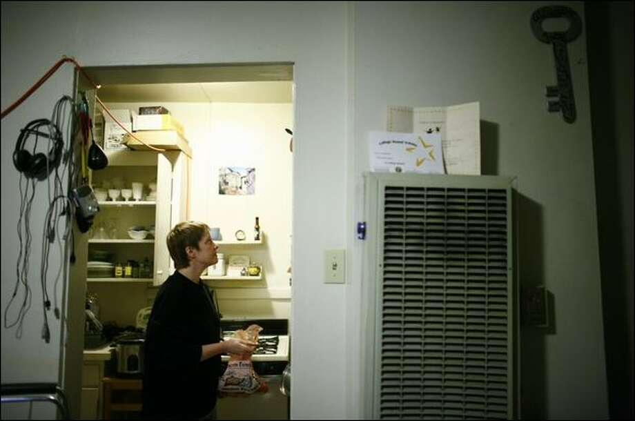 Hafoc Yates, a 49-year-old freelance Web designer, prepares food Wednesday for Thanksgiving in her Queen Anne apartment she shares with her son. Yates has stopped using the gas heater on the wall of her apartment and instead is learning to bake, and using the oven as a heat source. Photo: Joshua Trujillo/Seattle Post-Intelligencer