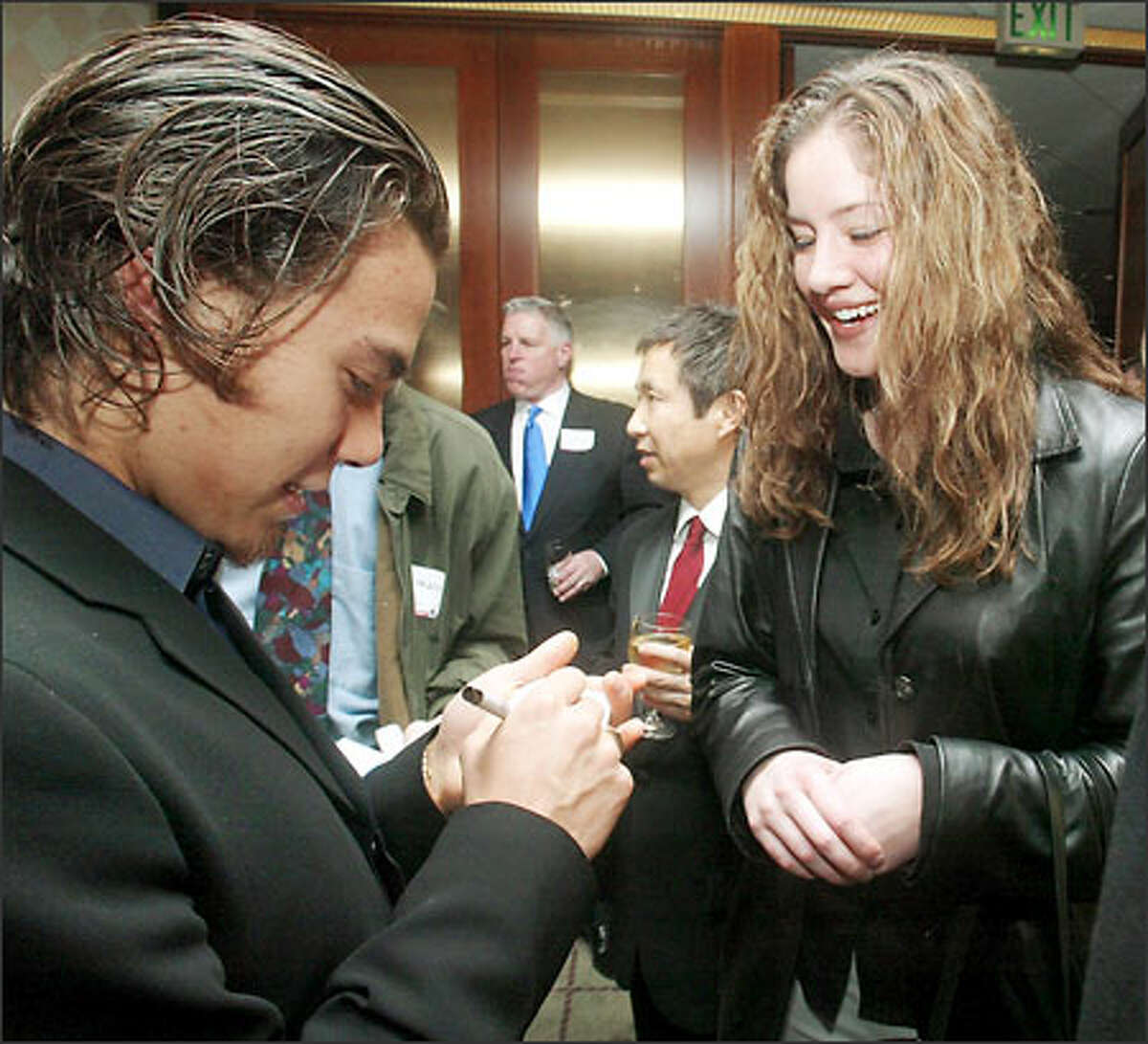 Short-track speedskating gold and silver medalist Apolo Anton Ohno signs a business card for fan Sandra Reed before the P-I Sports Star banquet at the Westin.