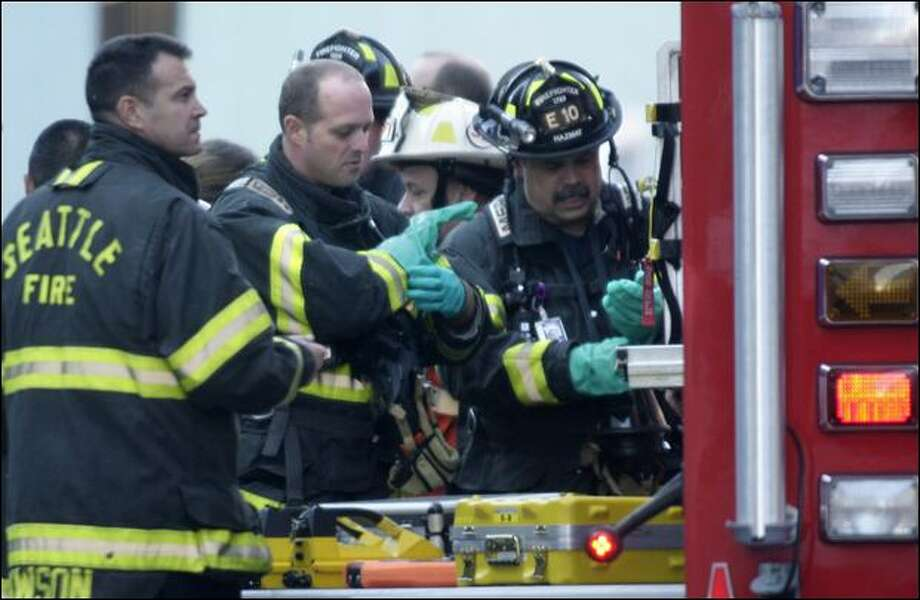 Seattle firefighters put on protective gloves Nov. 24 as they prepare to enter the 911 call center at Ninth Avenue and Virginia Street after a suspicious and potentially hazardous material was reported. Photo: Andy Rogers/Seattle Post-Intelligencer
