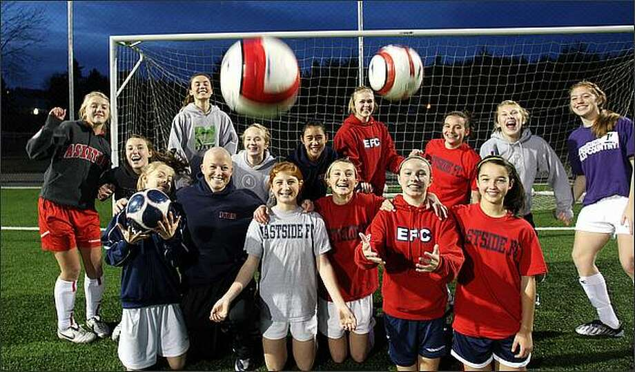As she fights non-Hodgkin's lymphoma, Michelle French, 31, the state's second-most-decorated women's soccer player, is back to coaching her three soccer teams, including the Girls' Under 14 Eastside Football Club Red team in Preston. French, second from left in the bottom row, is undergoing chemotherapy and has a 90 percent chance of recovery. Photo: Karen Ducey/Seattle Post-Intelligencer