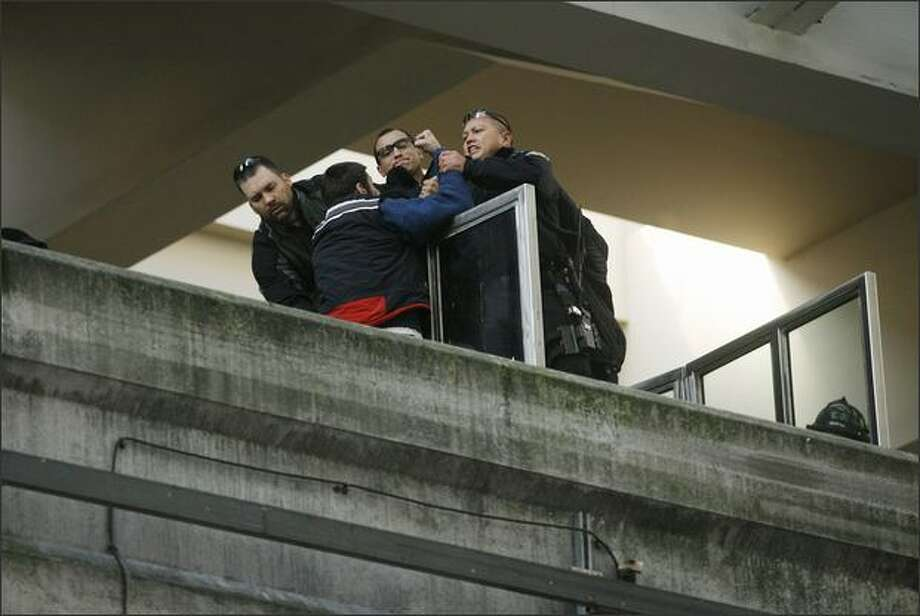 A man (back to camera) who climbed onto the Monorail at the Westlake Center is helped off the rail after surrendering to police in Seattle on Monday. Photo: Dan DeLong/Seattle Post-Intelligencer