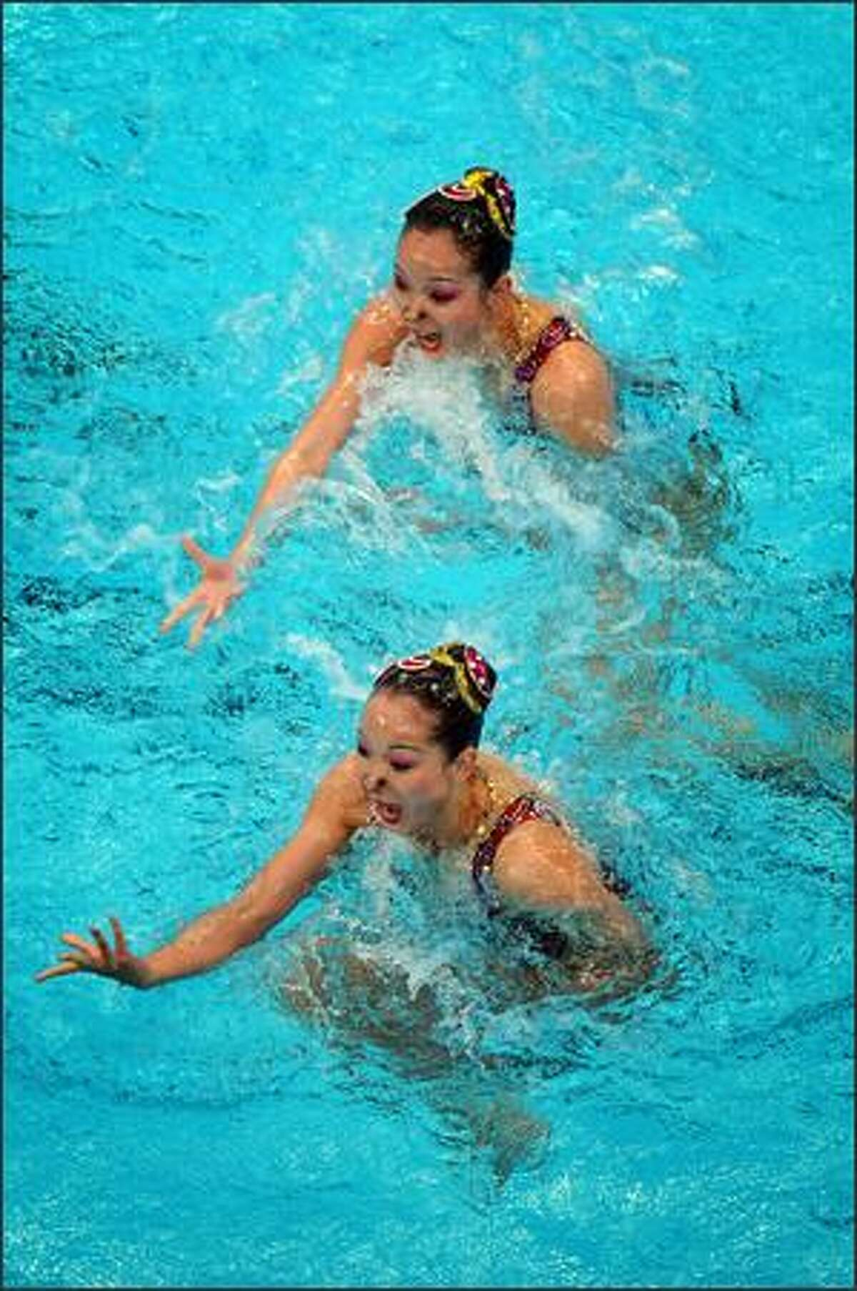 Japanese Saho Harada, top, and Emiko Suzuki perform during their synchronized swimming duet technical routine during the 2008 Beijing Olympic Games on Monday.