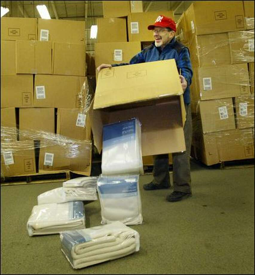 Volunteer Steve Lockitch opens a box containing blankets at a Forgotten Children's Fund warehouse in South Seattle. Photo: Karen Ducey/Seattle Post-Intelligencer