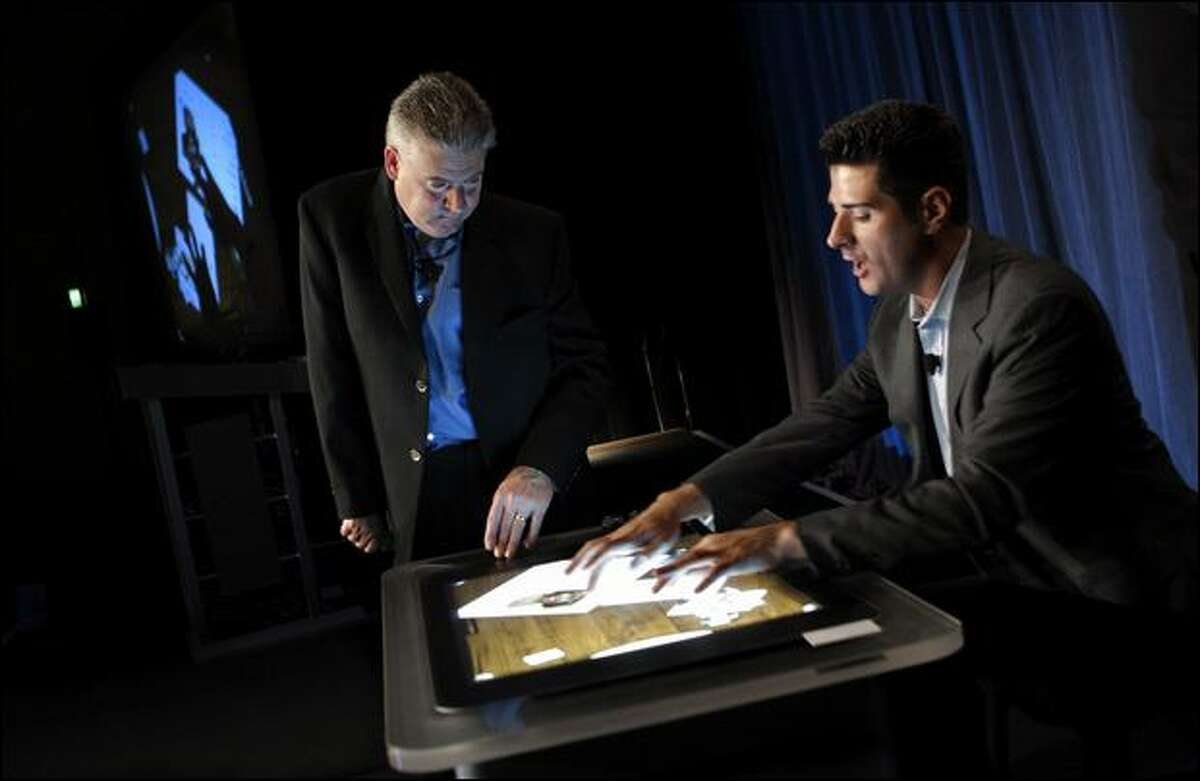Microsoft's Martin Bean, left, and Anthony Salcito demonstrate technologies that could be used in educational settings during a presentation on Tuesday at the School of the Future World Summit.