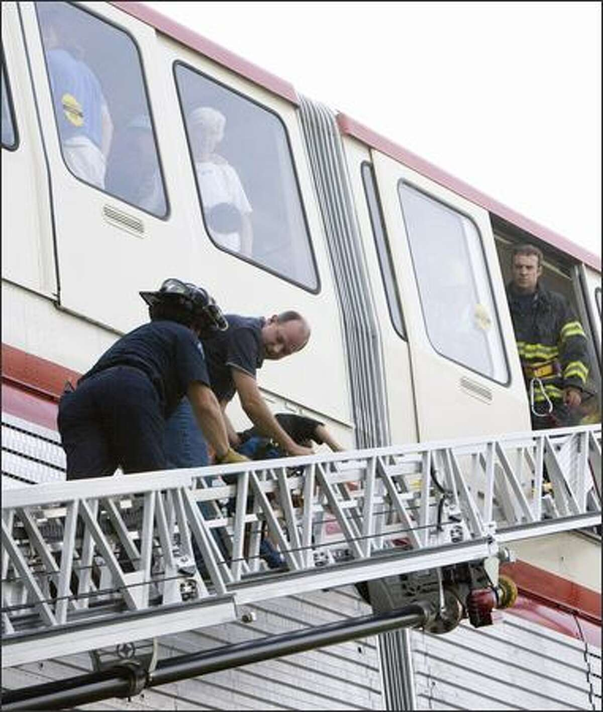 A firefighter (left) assists a monorail rider down a ladder.