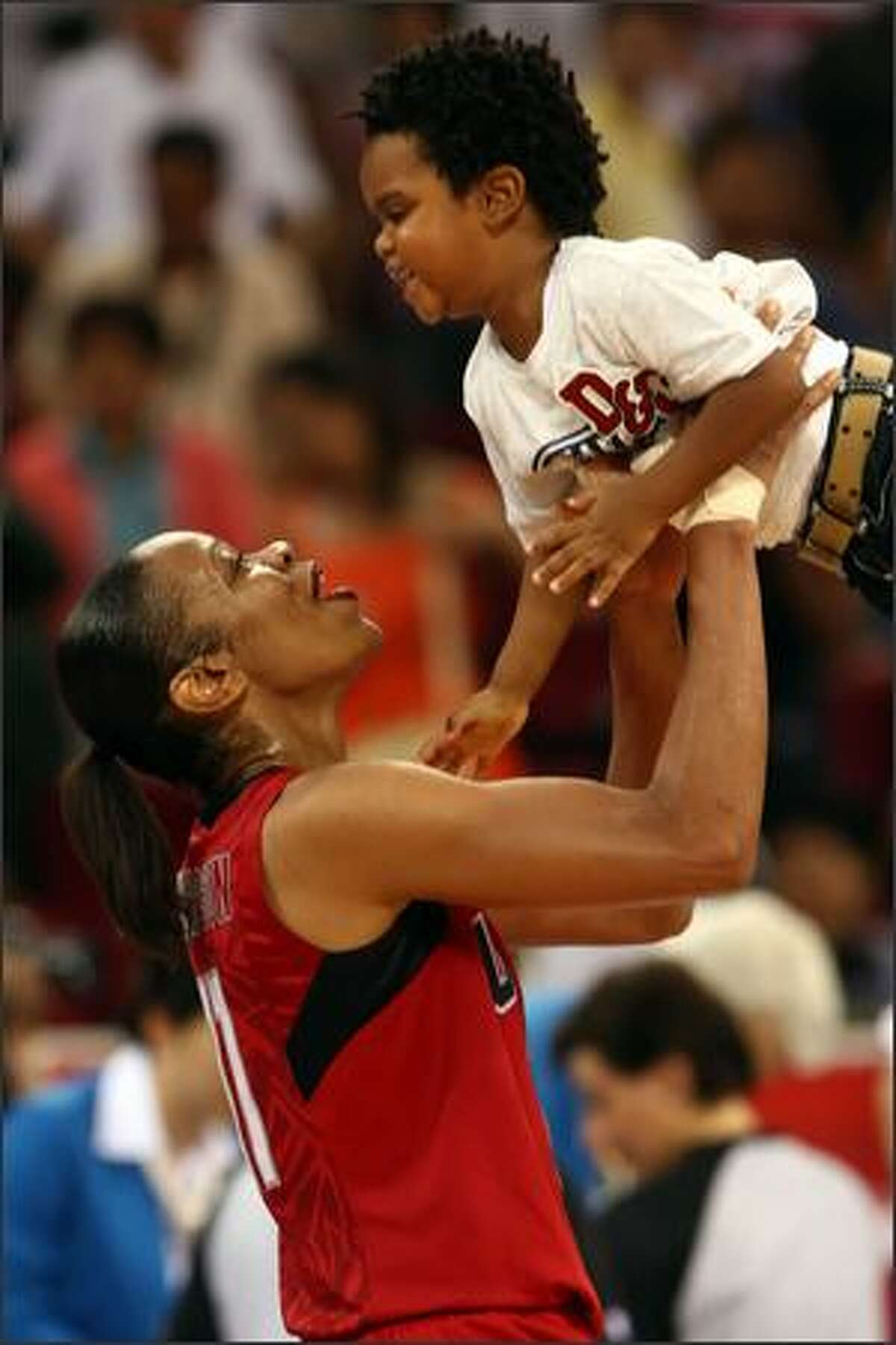 Tina Thompson of the United States celebrates with her son Dylan after the USA defeated Australia 92-65.