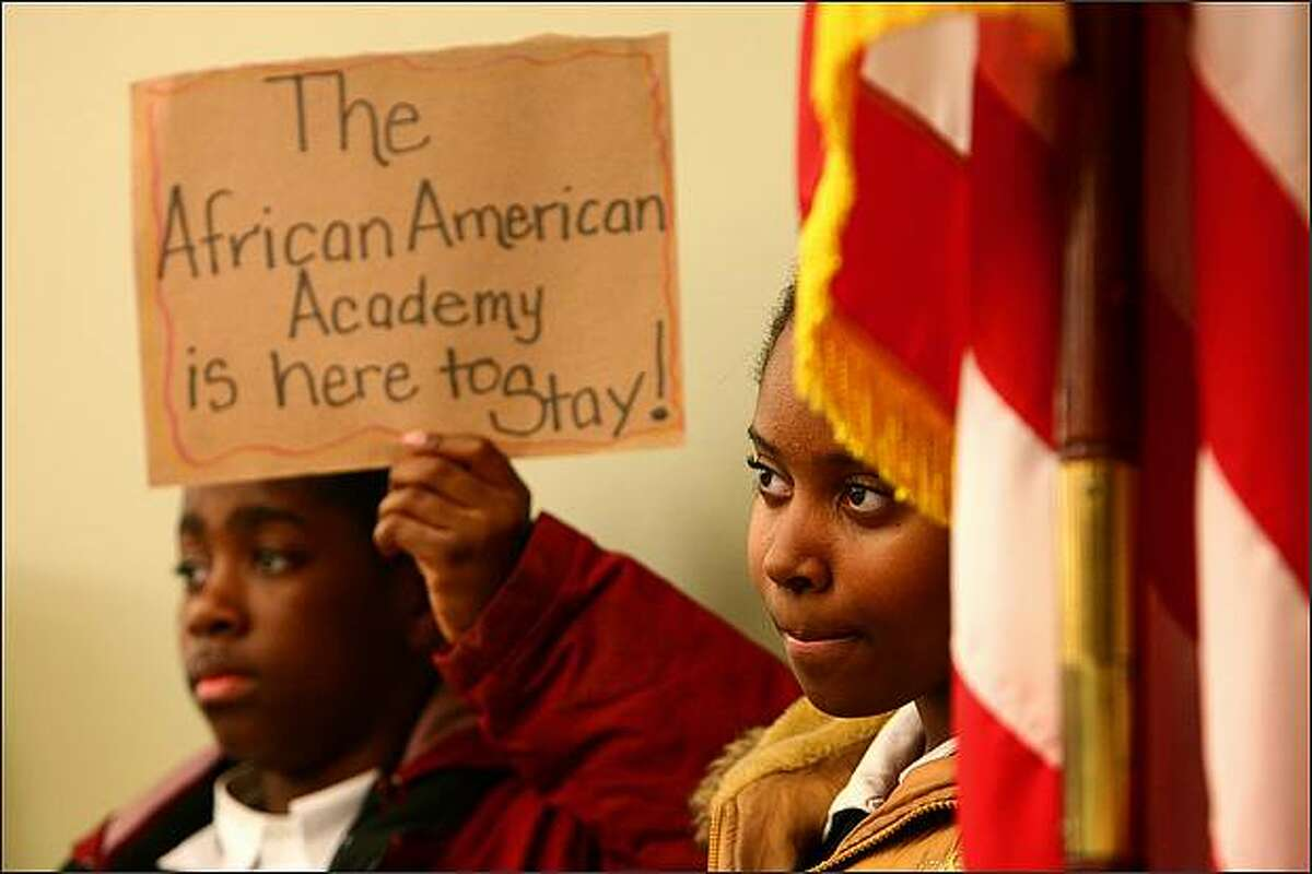 African American Academy students Breonn Hymes, 13, holding sign, and Nailah Kent, 11, right, attend a meeting of the Seattle Public Schools Board of Directors on Wednesday night at the John Stanford Center. The African American Academy is one of the schools that has been recommended for closure.