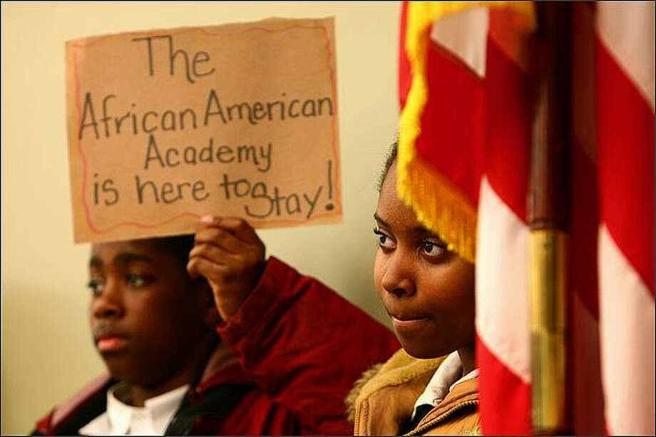 African American Academy students Breonn Hymes, 13, holding sign, and Nailah Kent, 11, right, attend a meeting of the Seattle Public Schools Board of Directors on Wednesday night at the John Stanford Center. The African American Academy is one of the schools that has been recommended for closure. Photo: Joshua Trujillo/Seattle Post-Intelligencer