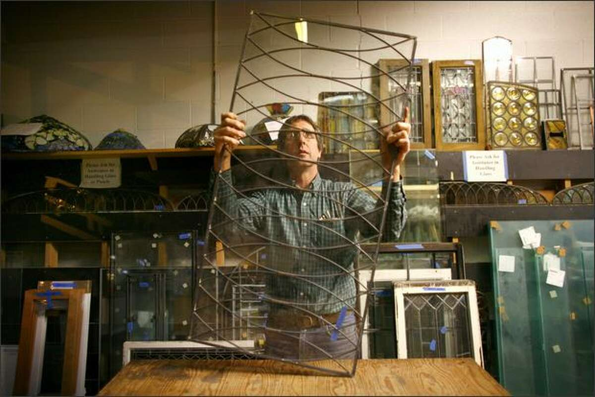 Jack Young, who has been working with leaded glass for decades, holds up a leaded window in the shop at Seattle Stained Glass.
