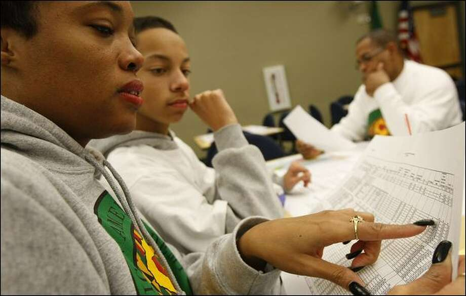 Angela Mealing and her son, Keano Debari, an eighth-grader at the African American Academy, look over data sheets about proposed school closures at a workshop Thursday. Photo: Brad Vest/Seattle Post-Intelligencer