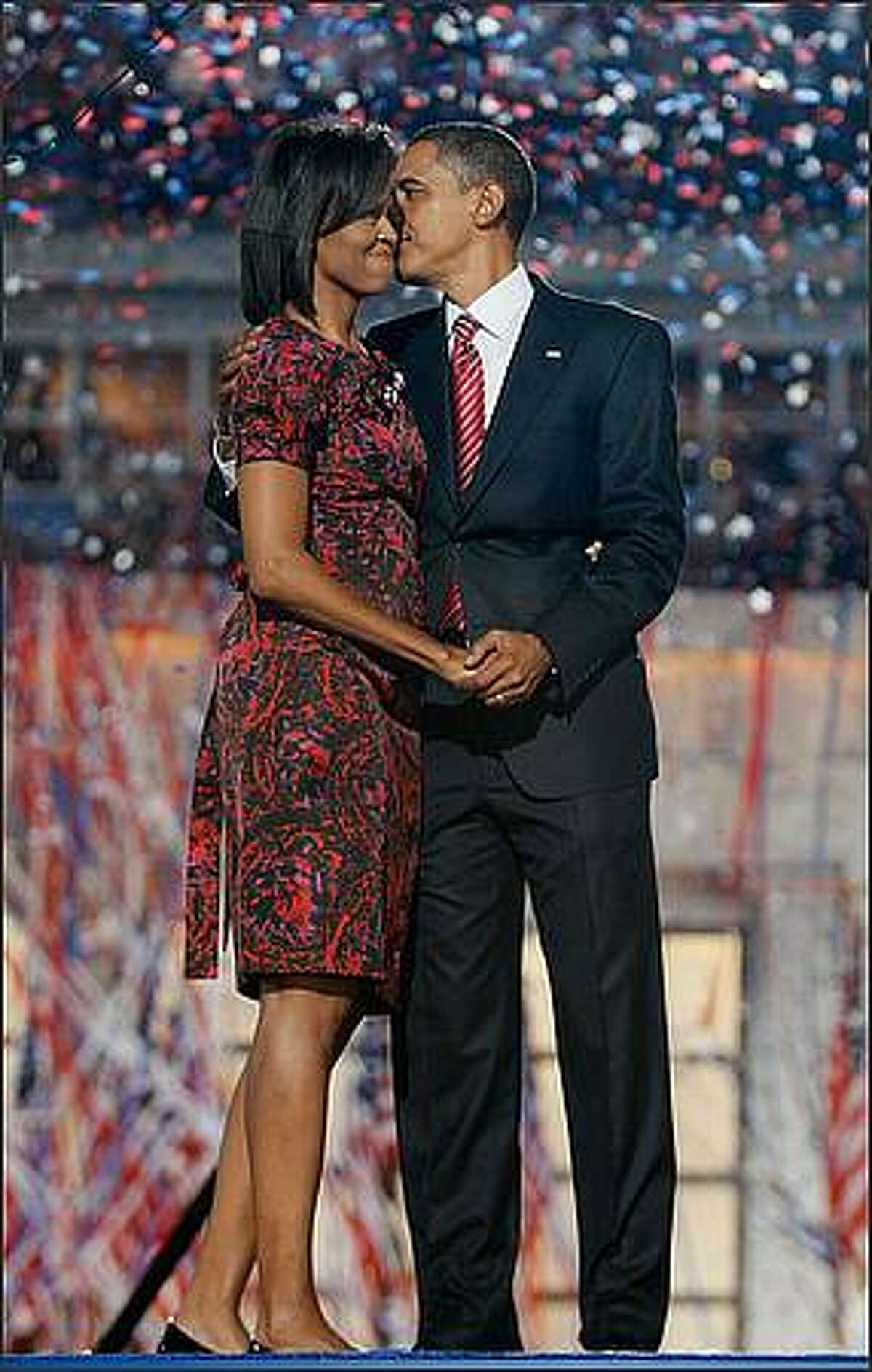 Democratic U.S. Presidential nominee Sen. Barack Obama (D-IL) (R) kisses his wife Michelle Obama after his speech on day four of the Democratic National Convention (DNC) at Invesco Field at Mile High in Denver, Colorado. U.S. Sen. Barack Obama (D-IL) is the first African-American to be officially nominated as a candidate for U.S. president by a major party. (Photo by Joe Raedle/Getty Images)