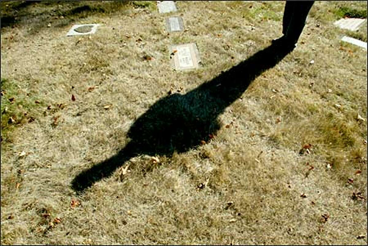 The shadow of Longview Memorial Park Cemetery sales manager John Miller flanks the unmarked grave of a Baby Jane Doe and the grave of a Jane Doe who is believed to be the baby's mother. Both were homicide victims and were found in two different rivers near Longview.