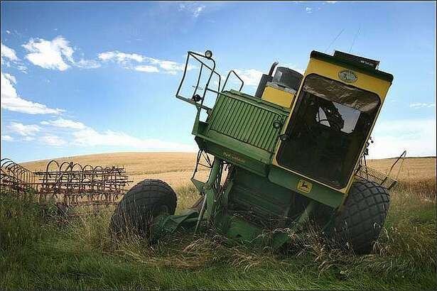 An old, broken-down combine leans towards the ground on the old Cochran farm outside of Garfield, Wash. Many abandoned machines appear as stationed relics seen along the local roads that weave throughout the Palouse region.