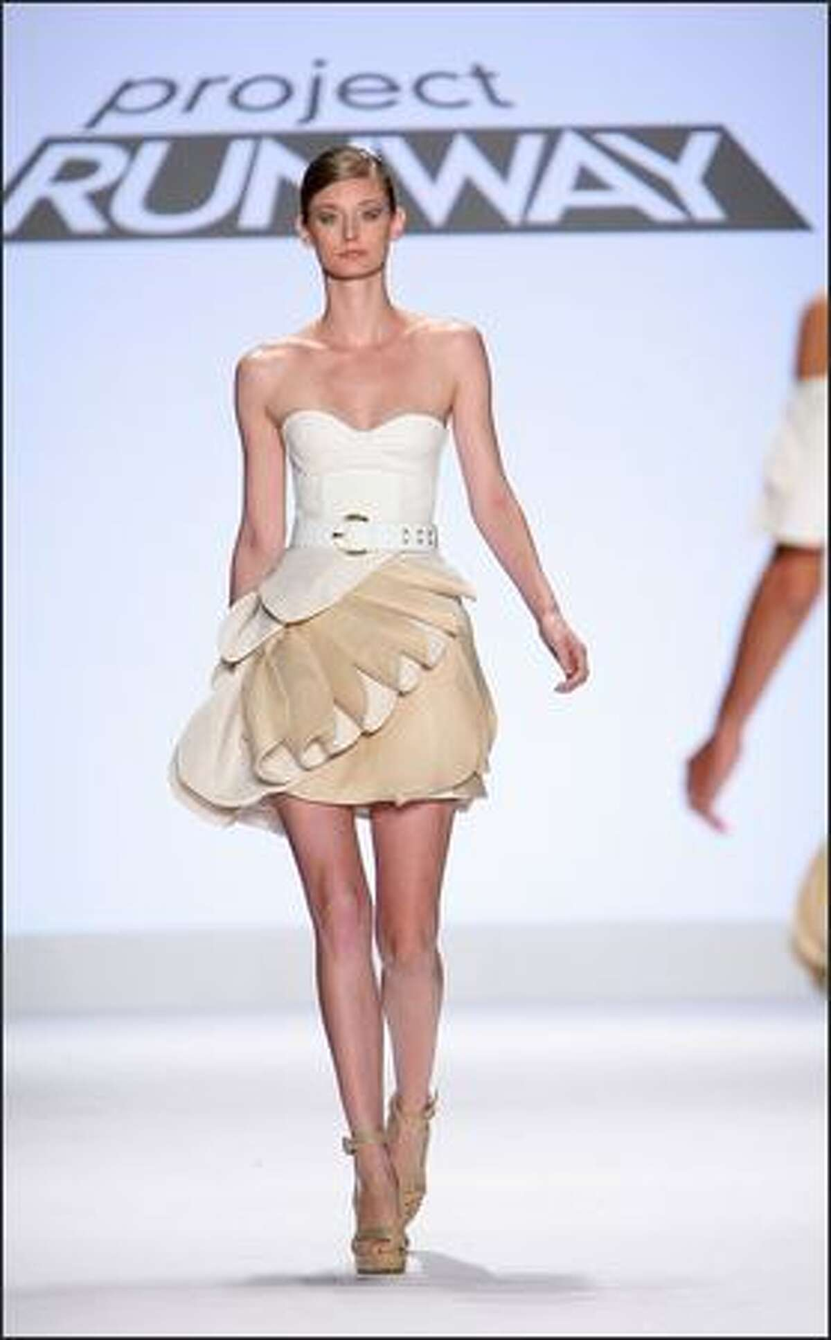 A model walks the runway wearing a dress designed by Leanne Marshall.
