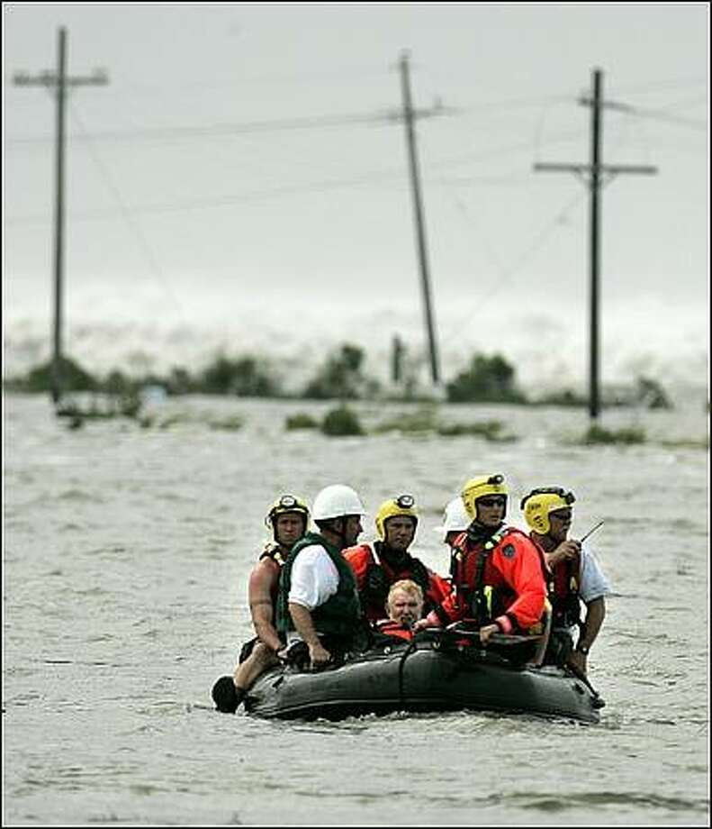 Bill Murphy, center, is taken to high ground by boat after his wife Barbara and two others were rescued by a Coast Guard helicopter in High Island, Texas as Hurricane Ike moves towards Texas. Murphy and his wife were leaving their home in Bolivar and stopped to pick up two stranded motorists when they became stranded too when rapidly rising water hit their truck(AP Photo/The Dallas Morning News, Guy Reynolds)