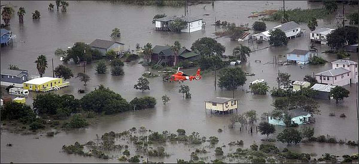 A U.S. Coast Guard helicopter flies over flooded Bolivar Peninsula, Texas as Hurricane Ike approaches. (AP Photo/David J. Phillip)