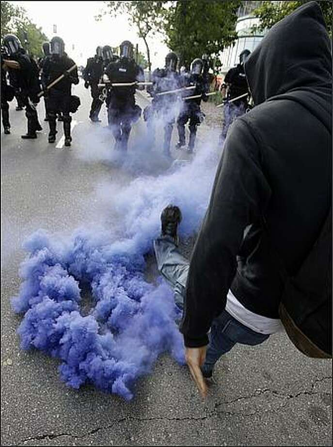 A protester kicks a smoke bomb during a protest at the Republican National Convention in St. Paul, Minn. Matt Rourke/AP