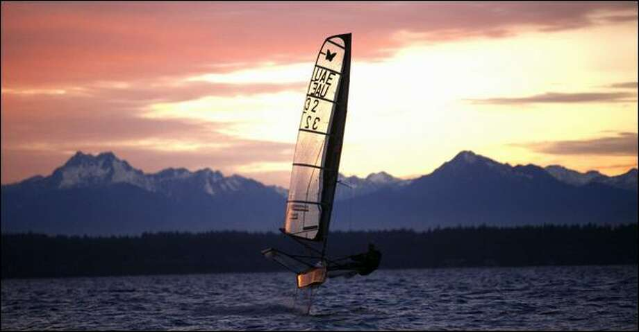 Dalton Bergan sails out of an Olympic Mountains sunset aboard his moth boat, which whizzes across the water on hydrofoils. Sailing hydrofoil moths is trickier than a regular sailboat; it has the added component of steering up and down. Photo: Joshua Trujillo/Seattle Post-Intelligencer