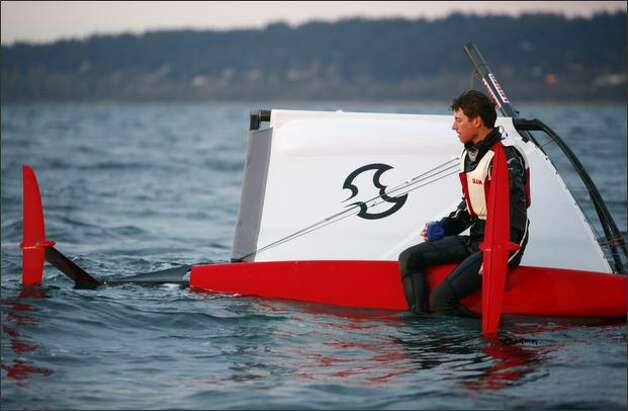 Matt Pistay sits atop his boat, hydrofoils exposed, after capsizing – which is quite a normal occurrence. Photo: Joshua Trujillo/Seattle Post-Intelligencer