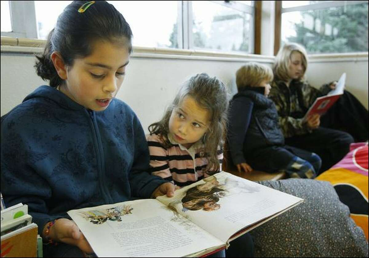 """Paola Sanchez, 10, reads """"Lancelot"""" with 5-year-old Gracie Semmens during a recent half-hour buddy session at the alternative Thornton Creek School."""
