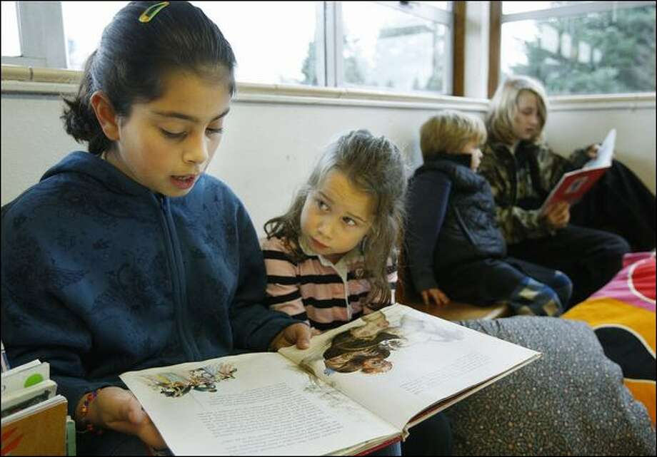 "Paola Sanchez, 10, reads ""Lancelot"" with 5-year-old Gracie Semmens during a recent half-hour buddy session at the alternative Thornton Creek School. Photo: Brad Vest/Seattle Post-Intelligencer"