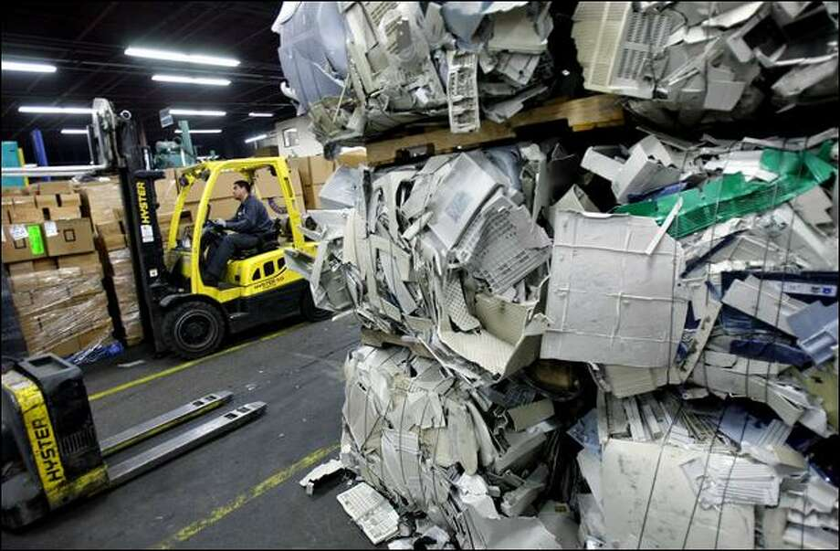 Electronics, including bales of compressed plastic, are processed Wednesday at Seattle's Total Reclaim, one of the recyclers where selected items will be shipped. Photo: Andy Rogers/Seattle Post-Intelligencer