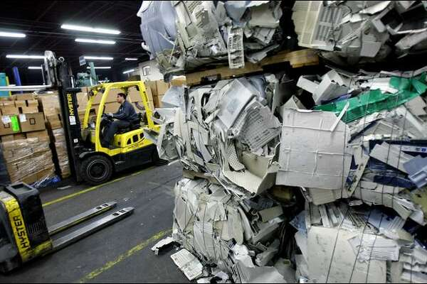 Electronics, including bales of compressed plastic, are processed Wednesday at Seattle's Total Reclaim, one of the recyclers where selected items will be shipped.