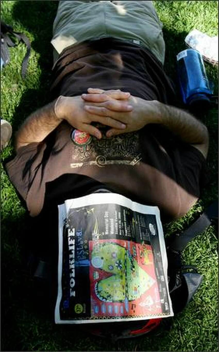 A music fan takes a rest with the help of a Northwest Folklife Festival program.
