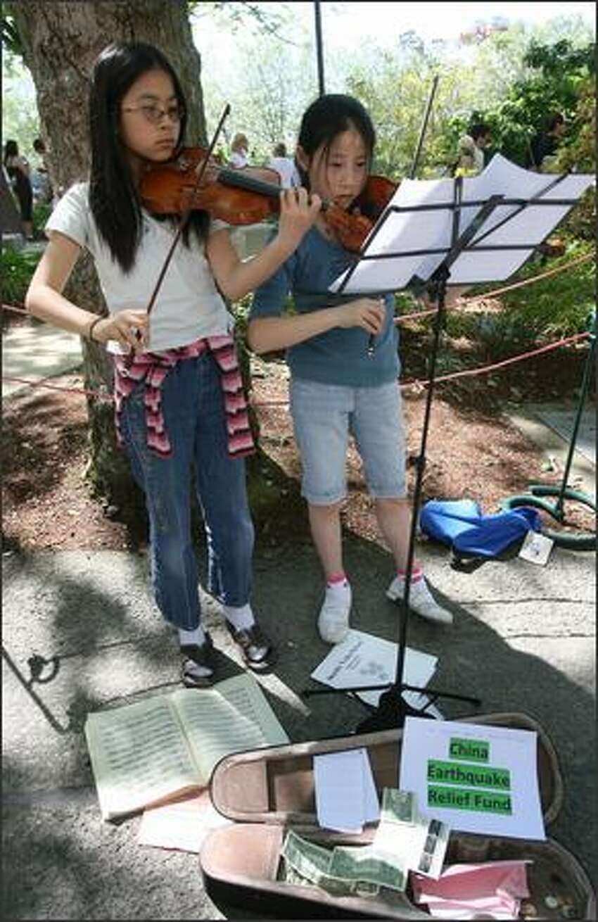 Sophie Ding, 11, left, and Elizabeth West, 12, both of Seattle, played violin to raise money for the Red Cross China Earthquake Relief Fund.