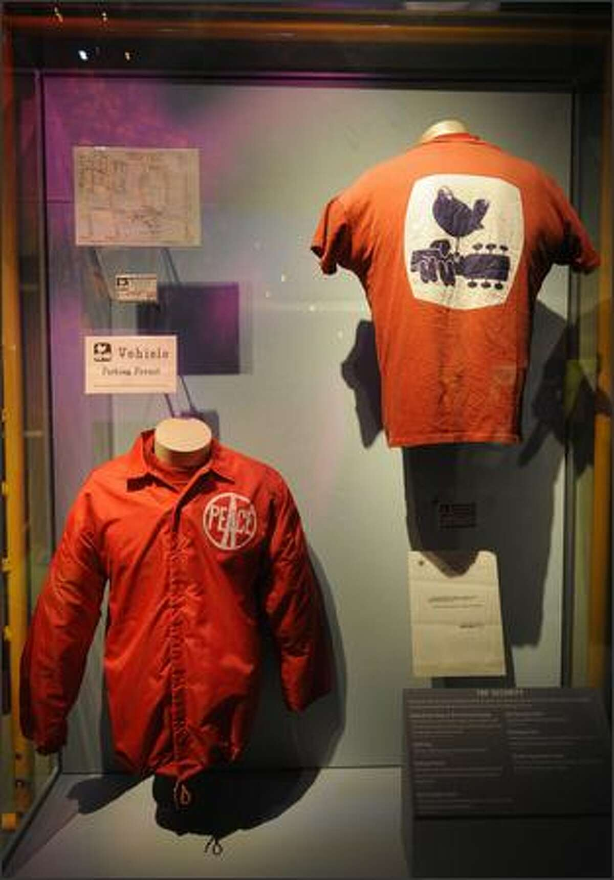 A T-shirt and a security personnel jacket from the Woodstock music festival are displayed.