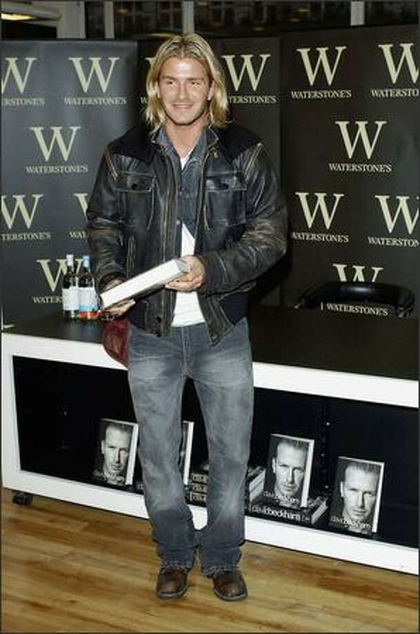 "David Beckham holds his autobiography ""My Side"" at the Waterstone's Book store in Piccadilly in London on Nov. 17, 2003. Photo: Getty Images"